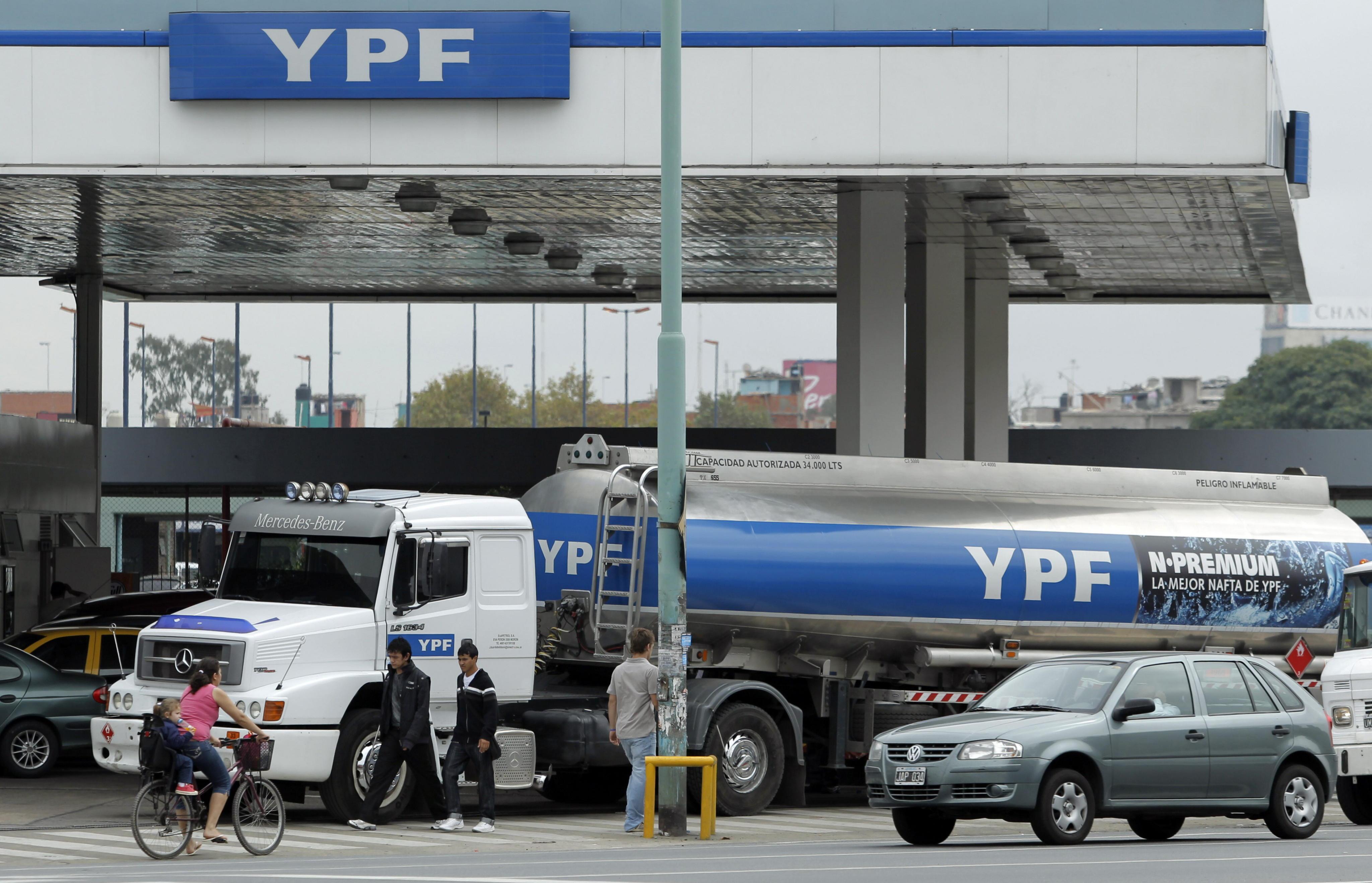 """BAS05. BUENOS AIRES (ARGENTINA), 12/04/2012 - Varias personas pasan hoy, jueves 12 de abril de 2012, frente a un camión cisterna de la petrolera YPF, en Buenos Aires. El ministro español de Industria, Energía y Turismo, José Manuel Soria, afirmó hoy que cualquier """"gesto de hostilidad"""" contra empresas de su país será interpretado como un gesto """"hacia España"""" y """"trae consigo consecuencias"""", en una aparente alusión al Gobierno argentino por el conflicto con YPF. Soria no citó en ningún momento al Gobierno argentino, que ha convocado para hoy a los gobernadores de las provincias petroleras para tratar sobre la situación de la compañía YPF, controlada por la española Repsol. EFE/Leo La Valle"""