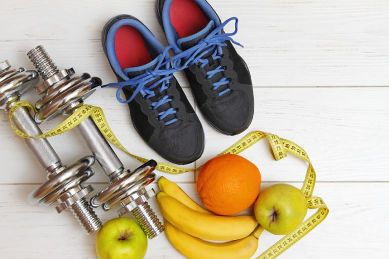 fitness equipment and healthy nutrition on white wooden plank floor